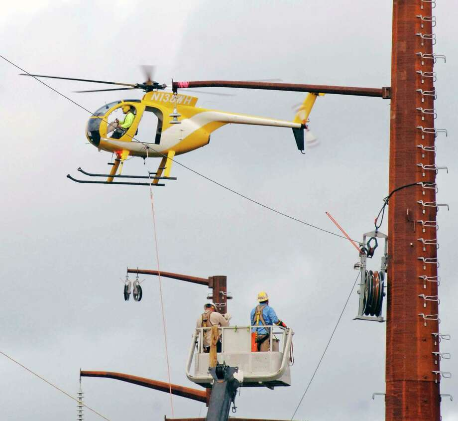 FILE PHOTO: An Eversource helicopter stringing new high-voltage transmission lines. The helicopter captured in photo is not the same as the one that will conduct the aeiral inspections. Photo: Contributed Photo