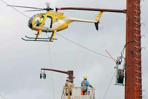 FILE PHOTO: An Eversource helicopter stringing new high-voltage transmission lines. The helicopter captured in photo is not the same as the one that will conduct the aeiral inspections.