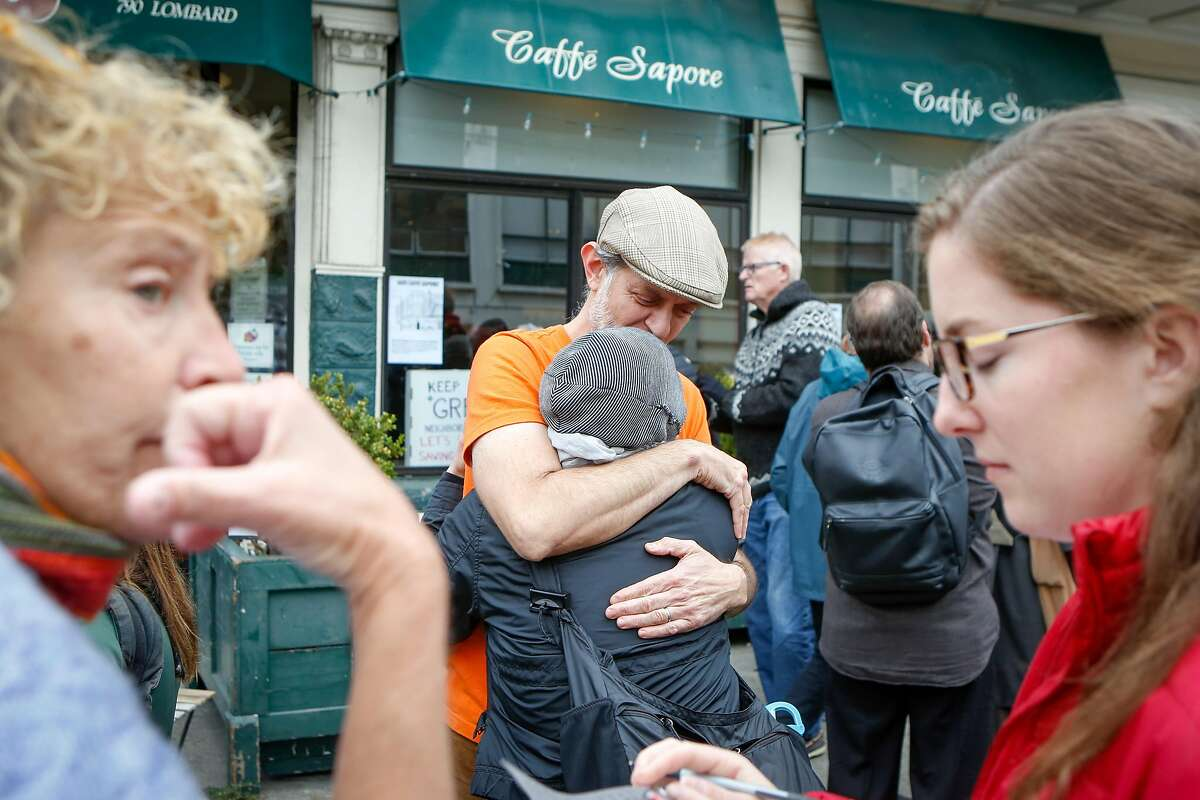 Owner of Caffe Sapore, Elias Bikahi, is greeted with hugs and support from neighbors and customers at a demonstration gathering in support of saving his long-time neighborhood cafe in North Beach San Francisco, Calif. on Thursday, Nov. 14, 2019.