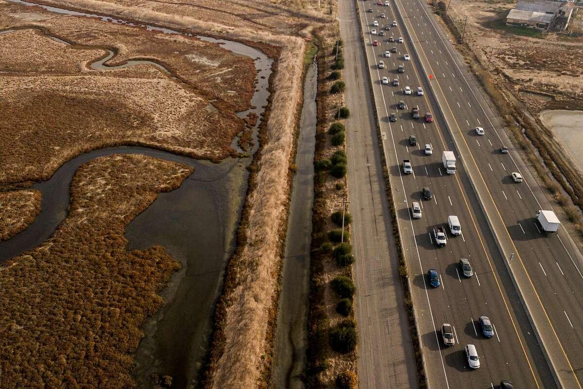 Cars on the left drive west towards the San Mateo-Hayward Bridge on Wednesday, Nov. 13, 2019, in Hayward, Calif.
