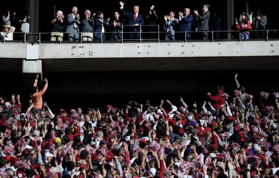 President Donald Trump and first lady Melania Trump are cheered during the LSU-Alabama football game.  But Trump was booed at a Washington Nationals game. A reader says this reflects the nation's historical divide. Photo: Brendan Smialowski /Getty Images / AFP or licensors