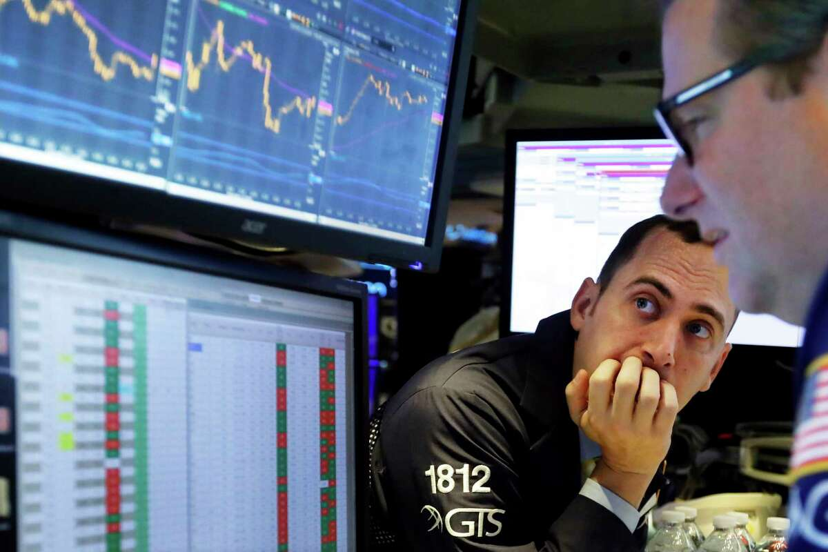 A pair of specialists work at the post that handles Walt Disney Co. on the floor of the New York Stock Exchange, Thursday, Nov. 14, 2019. Stocks are opening slightly lower on Wall Street led by a decline in technology companies. (AP Photo/Richard Drew)