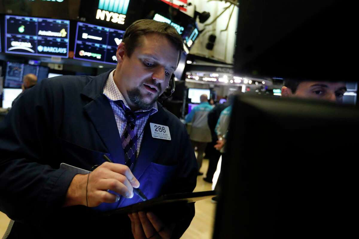 Trader Michale Milano, left, works on the floor of the New York Stock Exchange, Thursday, Nov. 14, 2019. Stocks are opening slightly lower on Wall Street led by a decline in technology companies. (AP Photo/Richard Drew)
