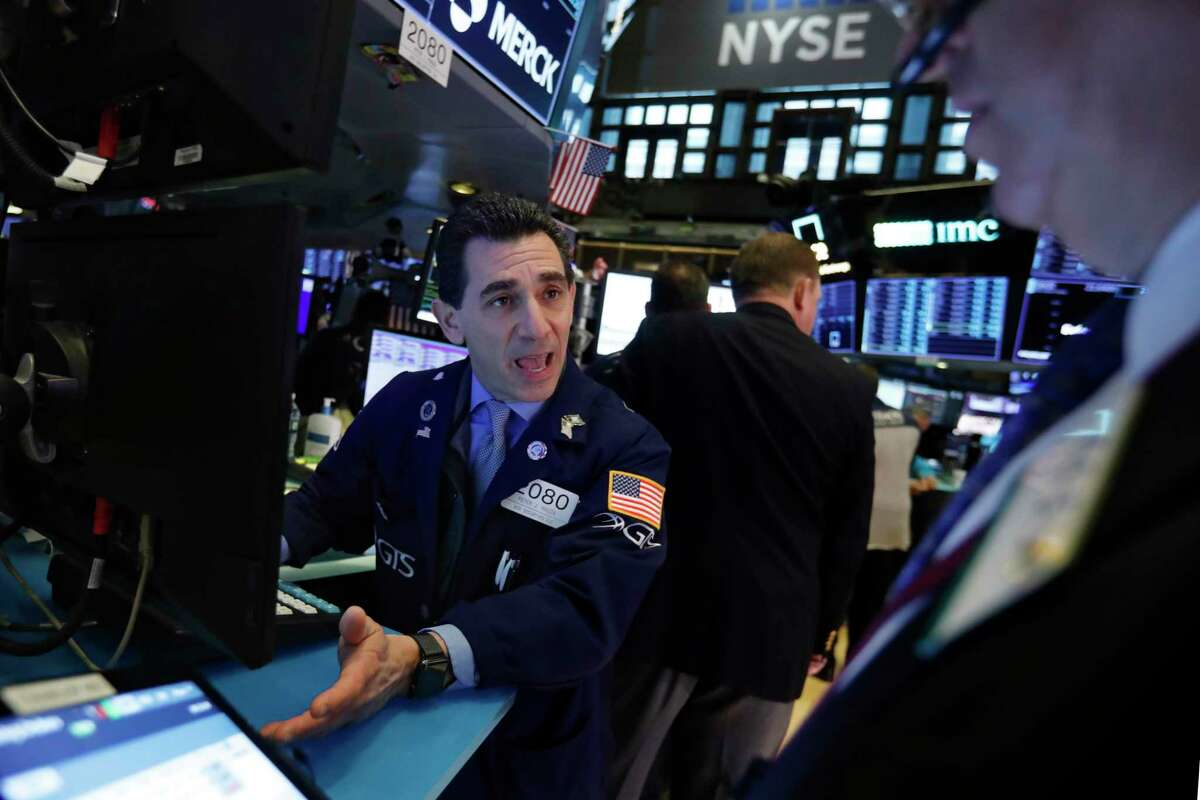 Specialist Peter Mazza, left, works at his post on the floor of the New York Stock Exchange, Thursday, Nov. 14, 2019. Stocks are opening slightly lower on Wall Street led by a decline in technology companies. (AP Photo/Richard Drew)
