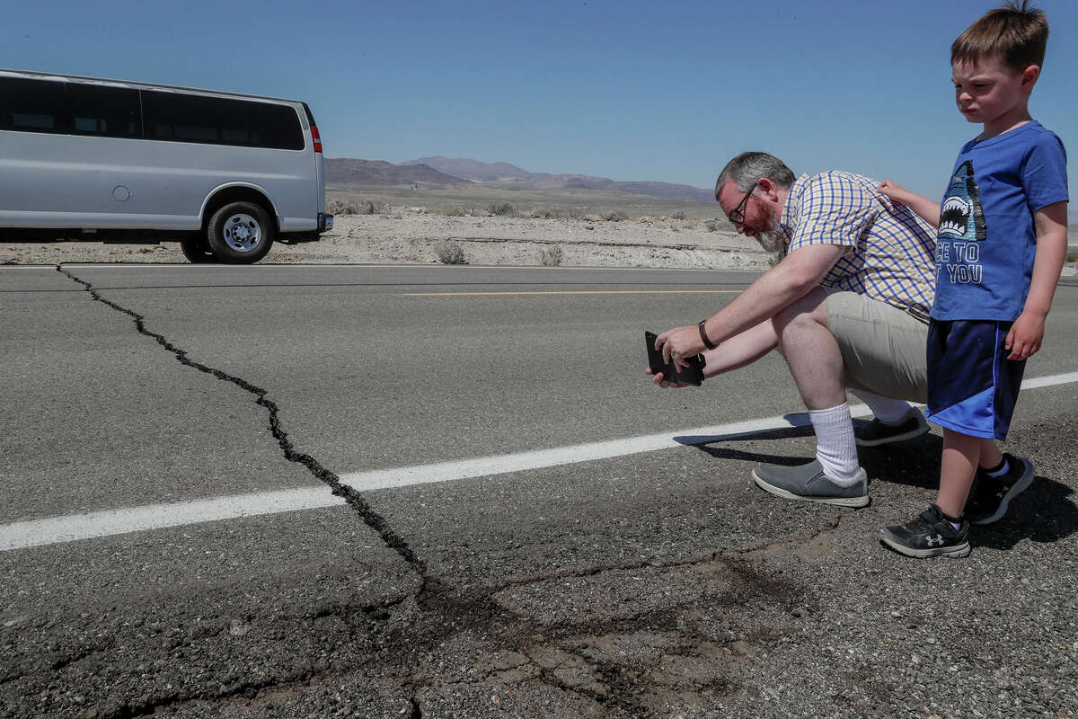 Andy Randolph and his son William stop for photos of a crack in California State Route 178 hours after a 6.4 magnitude earthquake struck the Searles Valley area on July 4, 2019 in Ridgecrest, Calif. New research shows that the Ridgecrest earthquakes that began in July ruptured at least two dozen faults. (Robert Gauthier/Los Angeles Times/TNS)