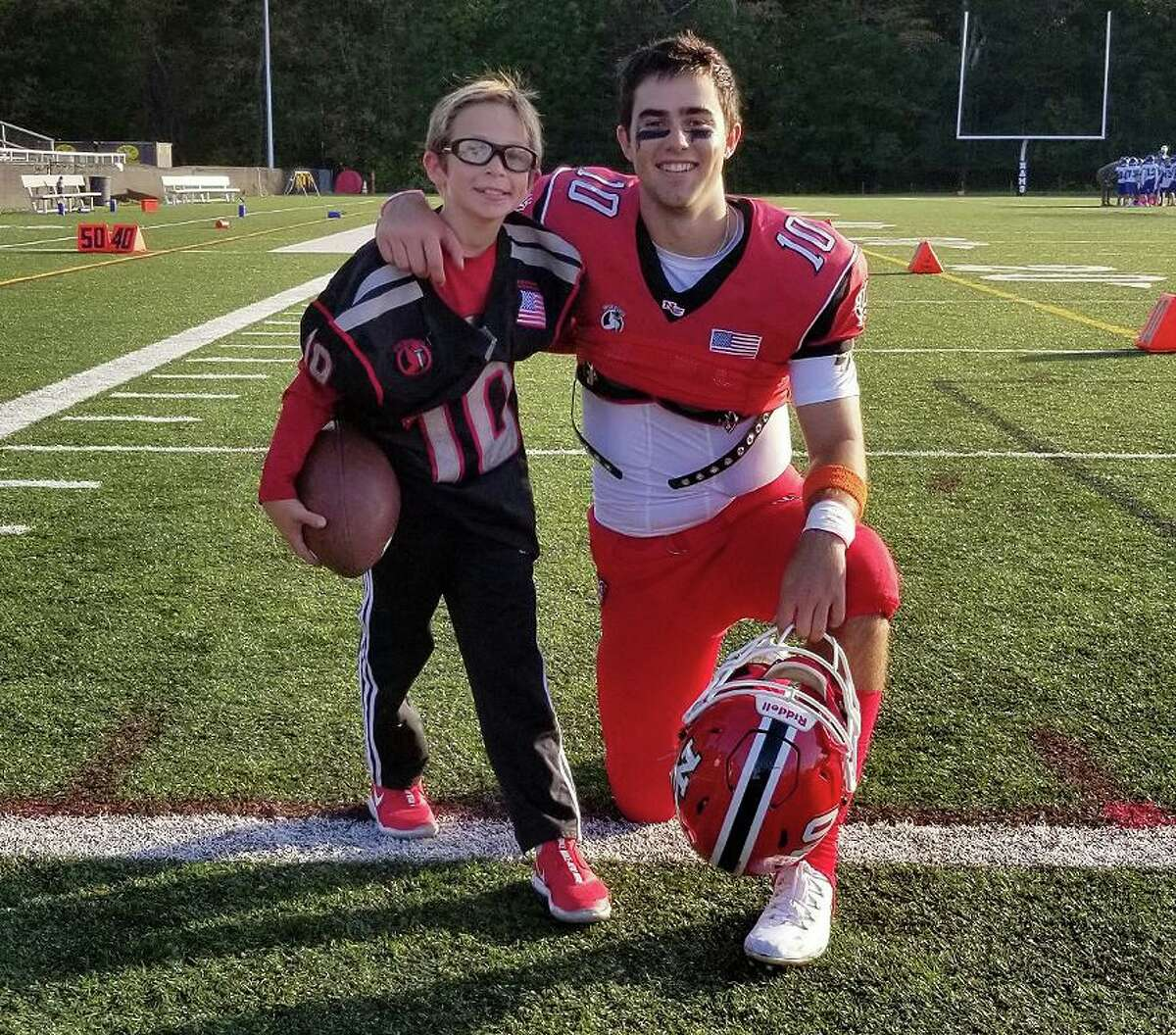 Ryan Berg, 8, and New Canaan senior Drew Pyne at Dunning Field for the Rams' homecoming football game on Saturday, Oct. 26, 2019.