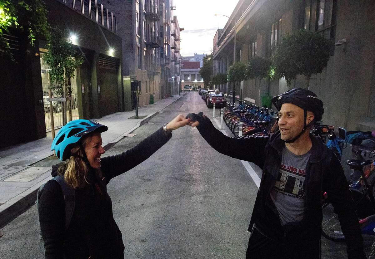 San Francisco Chronicle reporters Heather Knight (left) and Peter Hartlaub fist-bump after dropping off Bay Wheels bikes and finishing the first portion of their journey near Polk and Myrtle streets in San Francisco, Calif. Wednesday, September 4, 2019 as they attempt to traverse San Francisco�s 49-mile Scenic Drive without using a car.