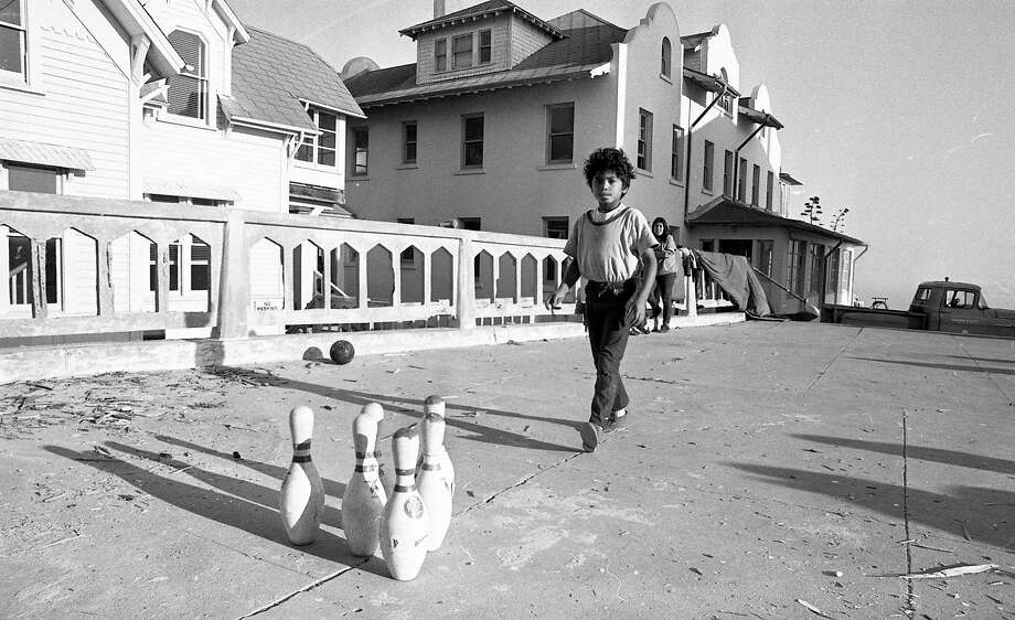 November 1969: Photo of the Native American occupation of Alcatraz. A boy, one of several children on the island, creates an outdoor bowling alley during the first few days of the occupation. Photo: Vincent Maggiora / The Chronicle