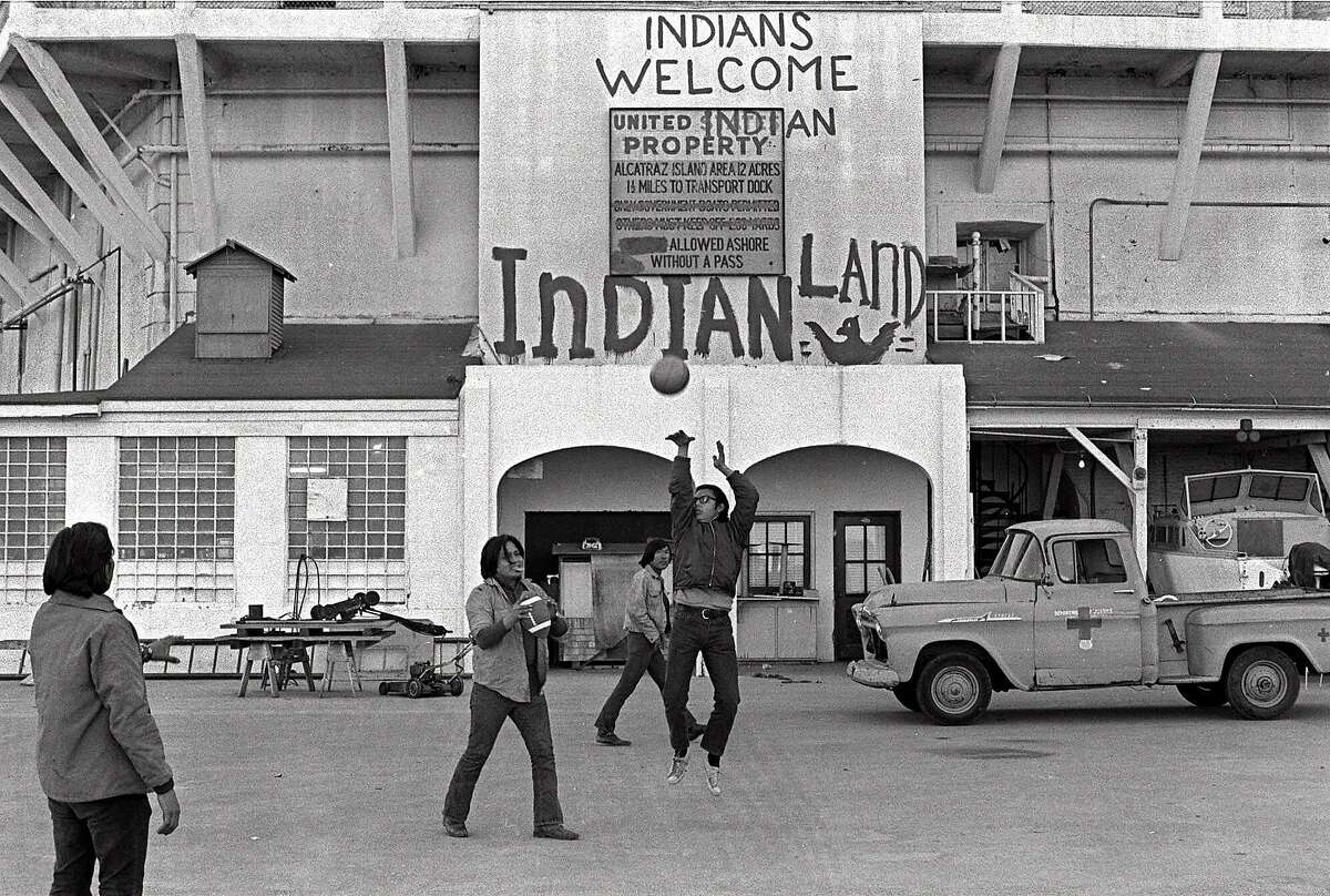 FILE--American Indians play ball games outside the prison wall on Alcatraz Island in San Francisco during their occupation of the island in this Nov. 26, 1969 file photo. The sign reading 'INDIANS WELCOME,' is one of the few physical reminders that 30 years ago a group of American Indians clung to the barren, bony slopes of Alcatraz for 19 months, winning the attention of the world and igniting a passion for civil rights. (AP Photo/File)