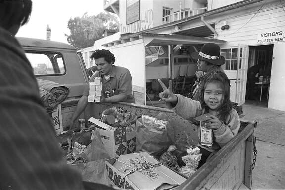 Richard Oakes unloading food that came over from SF by boat on November 20, 1969.  Richard's daughter, Yvonne, flashing the Victory sign, waits in the truck on the main dock on Alcatraz island.  Yvonne, was killed during the lengthy occupation by American Indians.