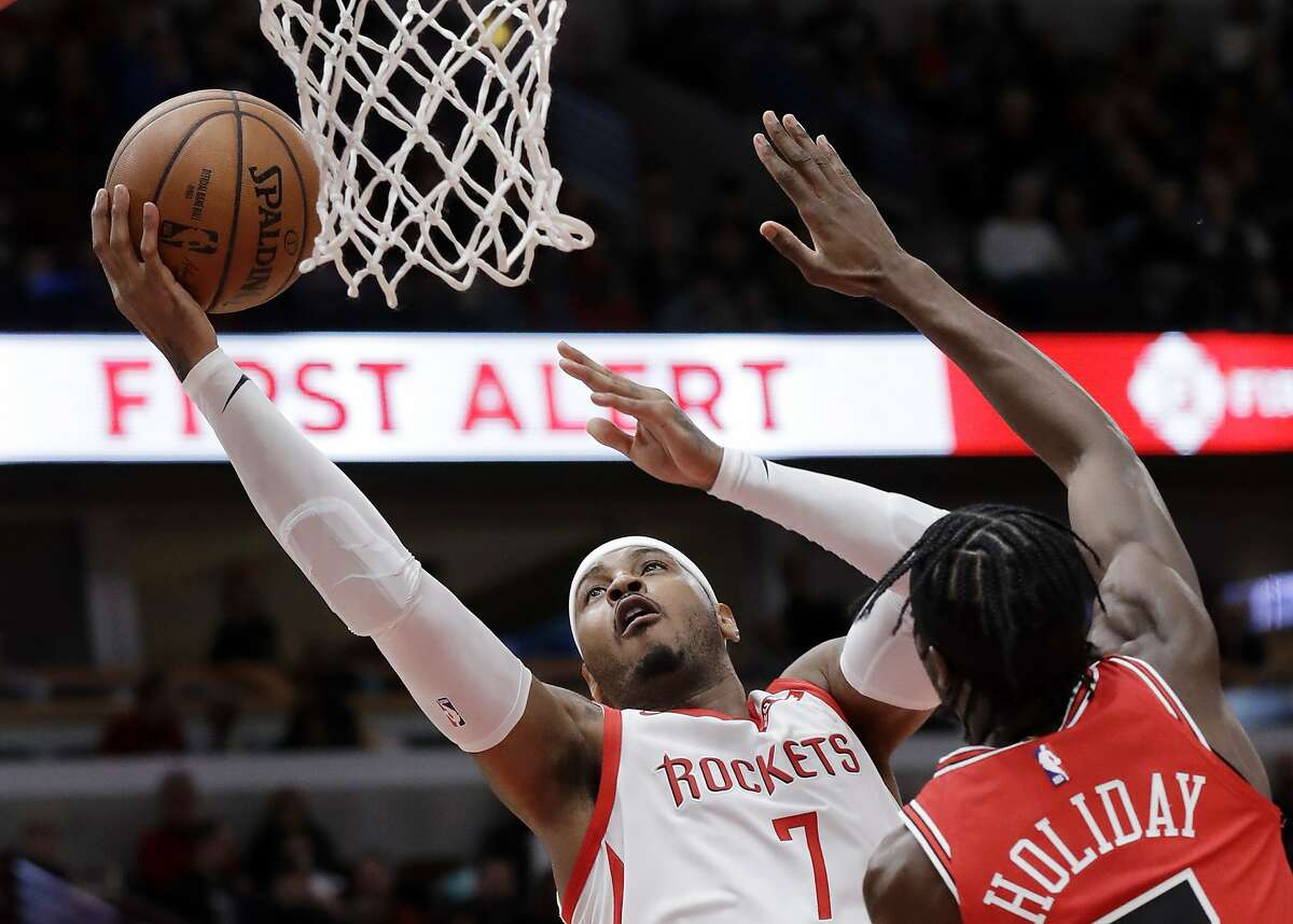 FILE - In this Nov. 3, 2018, file photo, Houston Rockets forward Carmelo Anthony, left, drives to the basket against Chicago Bulls forward Justin Holiday during the first half of an NBA basketball game in Chicago. A person familiar with the details says Anthony is returning to the NBA with the Portland Trail Blazers. The 10-time All-Star has not played since a short stint with the Rockets ended a little more than a year ago after just 10 games. (AP Photo/Nam Y. Huh, File)