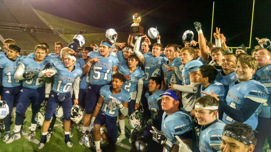 The Greenwood football team poses with the bi-district playoff trophy after beating Perryton 49-7 on Thursday in Canyon. Photo: Oscar LeRoy,  Reporter-Telegram