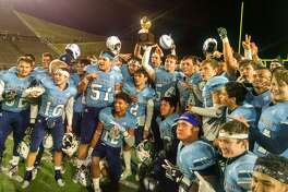 The Greenwood football team poses with the bi-district playoff trophy after beating Perryton 49-7 on Thursday in Canyon.