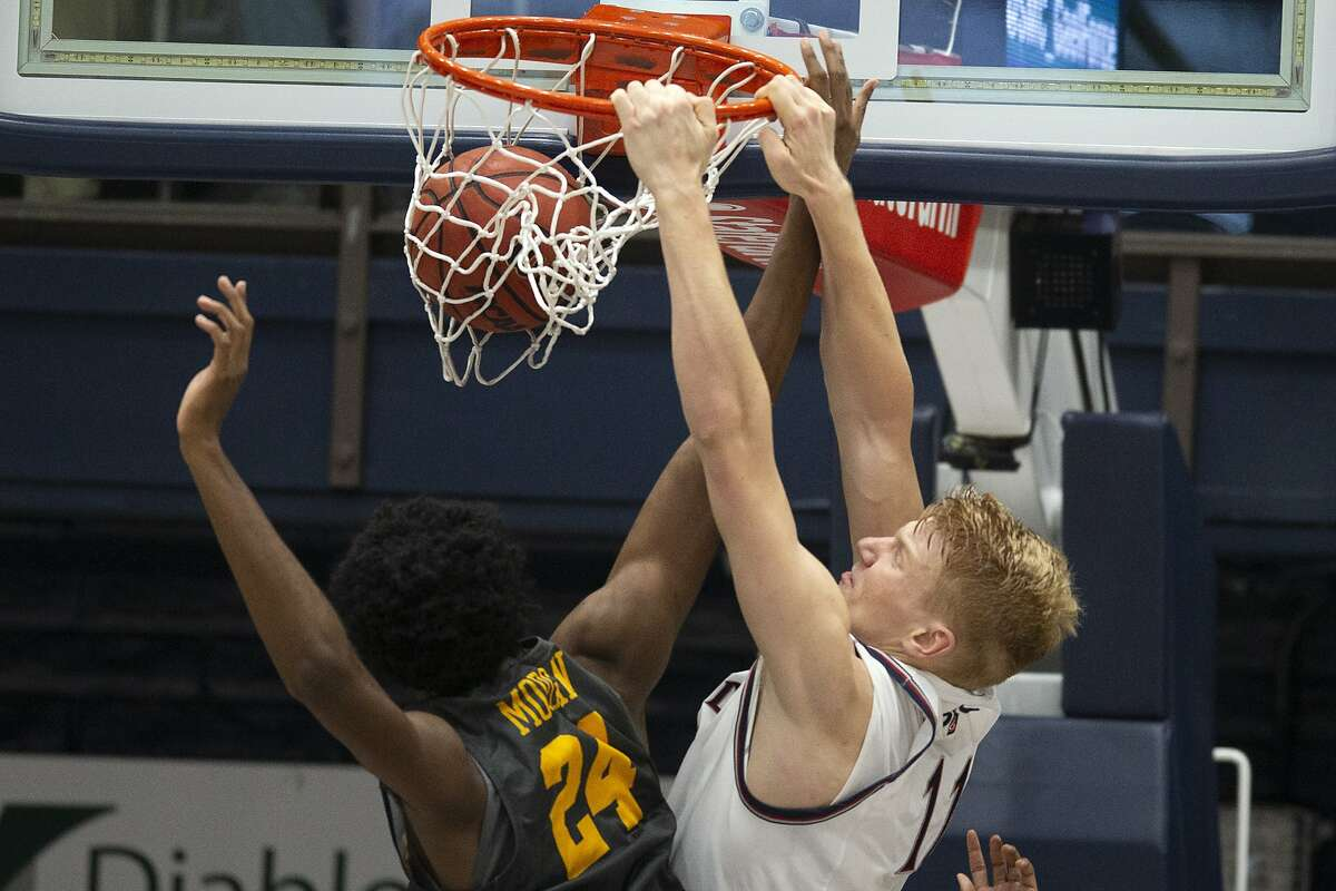 Saint Mary's forward Matthias Tass (11) dunks over Long Beach State center Joshua Morgan (24) during the first half of an NCAA college basketball game Thursday, Nov. 14, 2019, in Moraga, Calif. (AP Photo/D. Ross Cameron)