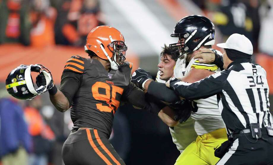 Cleveland Browns defensive end Myles Garrett, left, gets ready to hit Pittsburgh Steelers quarterback Mason Rudolph, second from left, with a helmet during the second half of an NFL football game Thursday, Nov. 14, 2019, in Cleveland. The Browns won 21-7. (AP Photo/Ron Schwane) Photo: Ron Schwane, Associated Press / Copyright 2019 The Associated Press. All rights reserved.