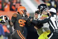 Cleveland Browns defensive end Myles Garrett, left, gets ready to hit Pittsburgh Steelers quarterback Mason Rudolph, second from left, with a helmet during the second half of an NFL football game Thursday, Nov. 14, 2019, in Cleveland. The Browns won 21-7. (AP Photo/Ron Schwane)