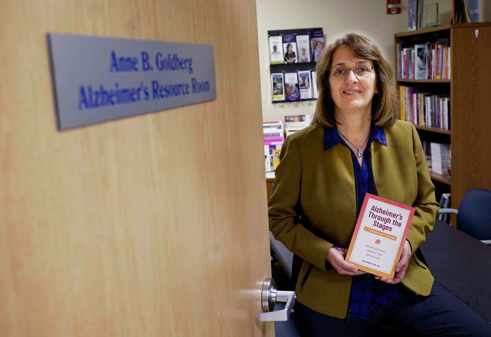 Mary Moller, program specialist, Center for Excellence for Alzheimer's Disease, Alzheimer's Center at Albany Med, poses for a photo with her book, Alzheimer's Through the Stages: A Caregiver's Guide, on Thursday, Nov. 14, 2019, in Albany, N.Y. (Paul Buckowski/Times Union)