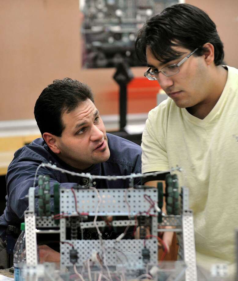 Team advisor Erik Savoyski, left, talks with Konstantinos Filippakos during an after-school work day for the Team 5150 robotics at Danbury High School on Thursday, Nov. 15, 2012. Photo: Jason Rearick / Jason Rearick / The News-Times