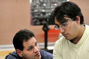 Team advisor Erik Savoyski, left, talks with Konstantinos Filippakos during an after-school work day for the Team 5150 robotics at Danbury High School on Thursday, Nov. 15, 2012.