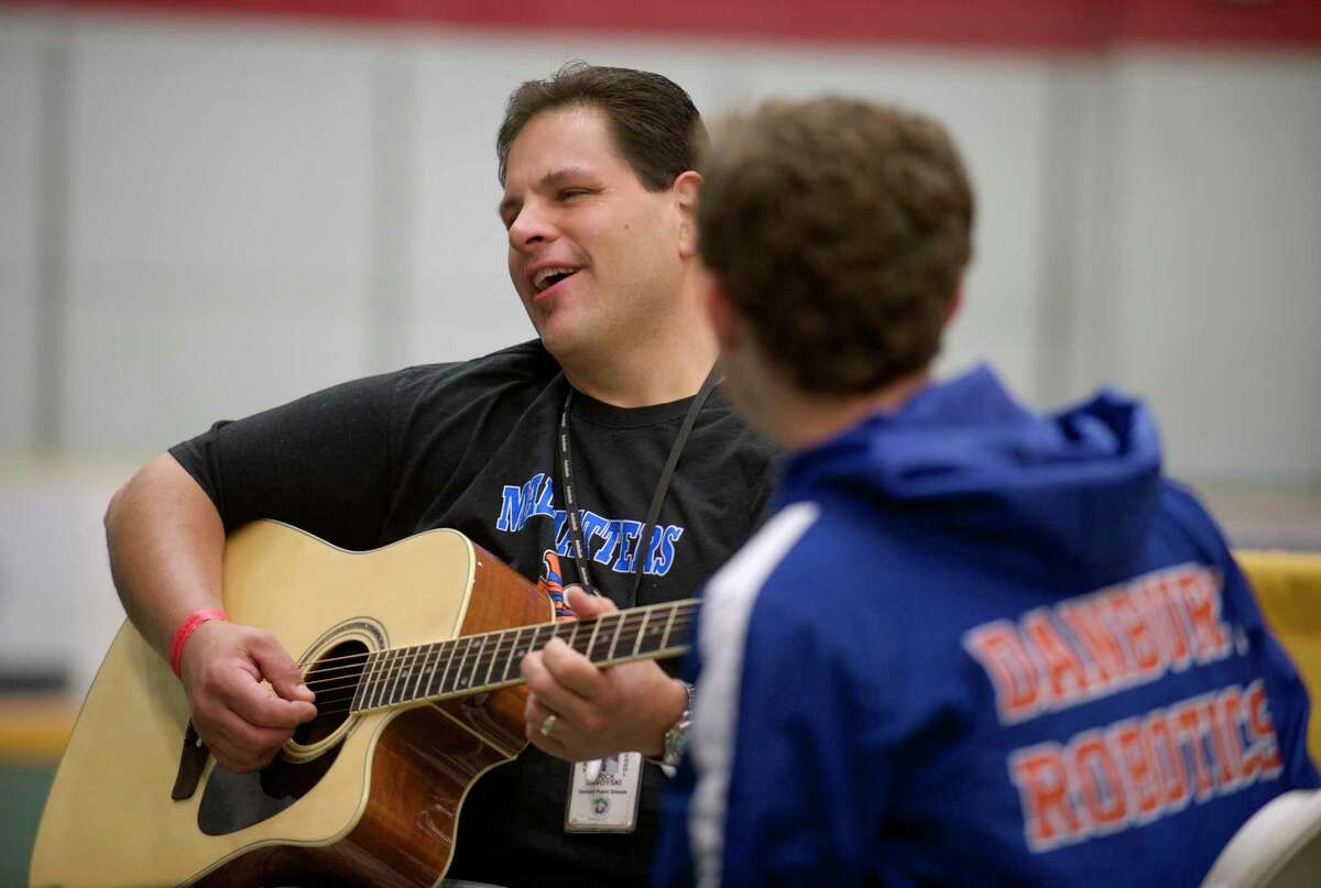 """Erik Savoyski, an advisor with Team 5150 Mad Hatter, a robotics team from Danbury High School, plays a guitar that was on display by Guitar Center, which had an exhibit set up in the Danbury Ice Arena for the 2014 Mad Hackers event, """"A Day of Innovation, Technology & Social Media"""", which took place in Danbury, Conn, on Saturday, June 6, 2014. Ben Albano, 17, a member of his team listens."""