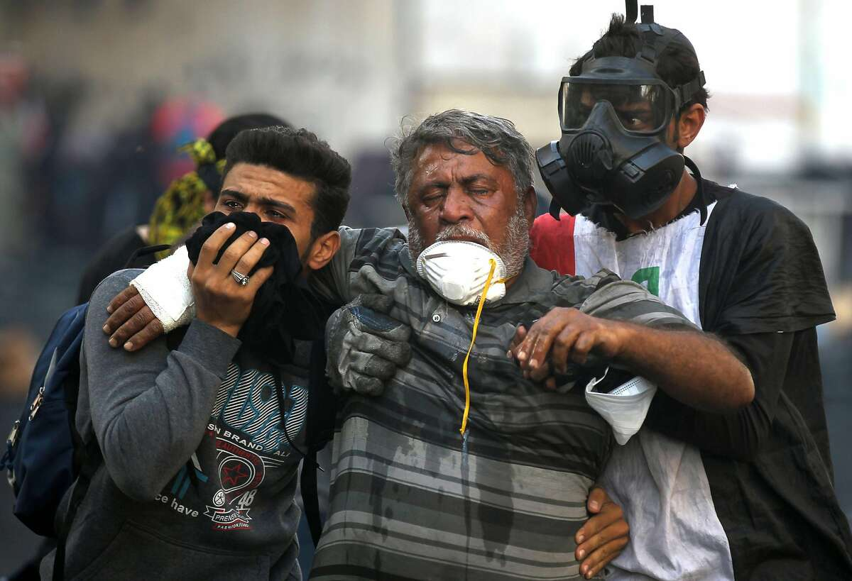 Iraqi volunteers help a protester affect by tear gas fired by security forces amid clashes at Baghdad's Khallani square during ongoing anti-government demonstrations on November 15, 2019. - Iraq's political elite has come under renewed pressure in recent days from both the street and the international community to seriously address calls for reform. (Photo by AHMAD AL-RUBAYE / AFP) (Photo by AHMAD AL-RUBAYE/AFP via Getty Images)