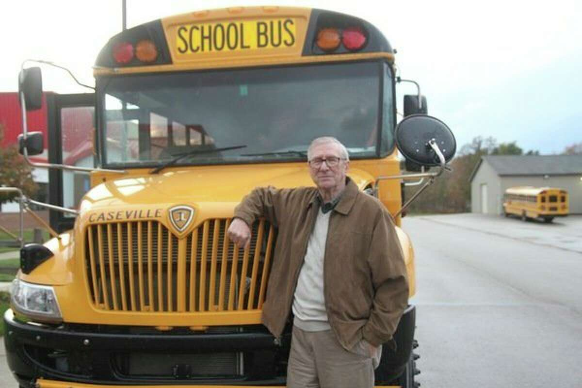 Jim Stahl leans against a Caseville Public Schools bus. Stahl once drove buses for the district, helping transport students to sporting events.(Rich Harp/Huron Daily Tribune)