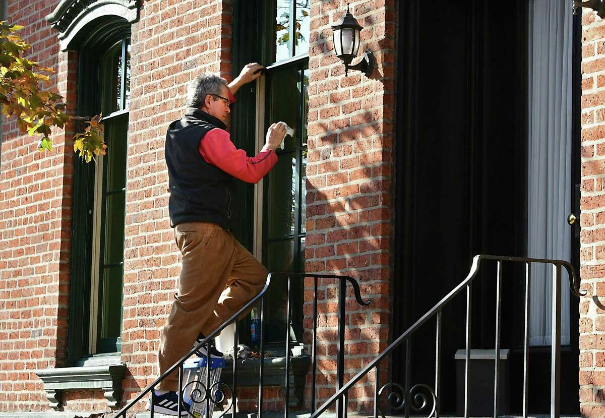 Peter Grimm cleans the windows of his home on 2nd St. in early preparation for annual Troy Victorian Stroll on Friday, Nov. 15, 2019 in Troy, N.Y. (Lori Van Buren/Times Union)