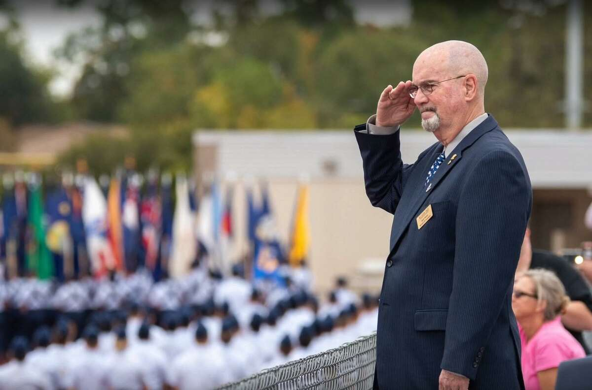 Rick Mann, Klein ISD's longest-tenured school board member, and a U.S. Air Force veteran, salutes during a past event. He was honored during his last school board meeting as a trustee on Nov. 11, 2019.