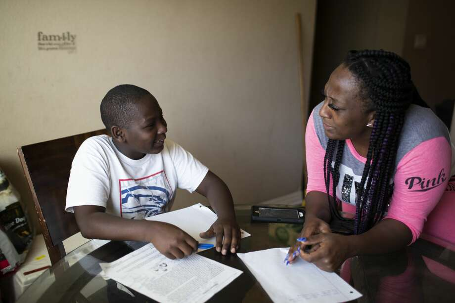 Nicholas, 13, works on his homework with his mother Britany Miller at home in Houston. Davis is an eighth grader at The Lawson Academy. Photo: Marie D. De Jesús/Staff Photographer