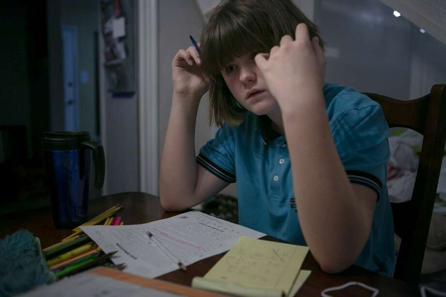 Ella Smith, 11, does math homework at the dining room table in her home in San Antonio. Photo: Josie Norris/Staff Photographer