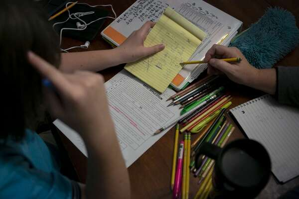 Jenn Smith helps her daughter Ella Smith, 11, with math homework at the dining room table in their home in San Antonio. (Josie Norris/Staff photographer | San Antonio Express-News)