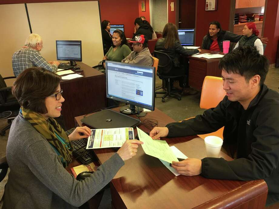 Cristina Cave, community relations senior manager for BakerRipley, helps complete a neighbor's tax return at one of 11 free preparation centers across the Houston area last year. Currently, BakerRipley is seeking volunteers to help taxpayers keep all their refunds during the new tax season. Photo: Courtesy By BakerRipley