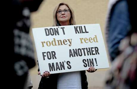 A woman holds a sign during a protest against the execution of Rodney Reed on Wednesday, Nov. 13, 2019, in Bastrop, Texas. Protesters rallied in support of Rodney Reed's campaign to stop his scheduled Nov. 20 execution for the 1996 killing of a 19-year-old Stacy Stites. New evidence in the case has led a growing number of Texas legislators, religious leaders and celebrities to press Gov. Greg Abbott to intervene.