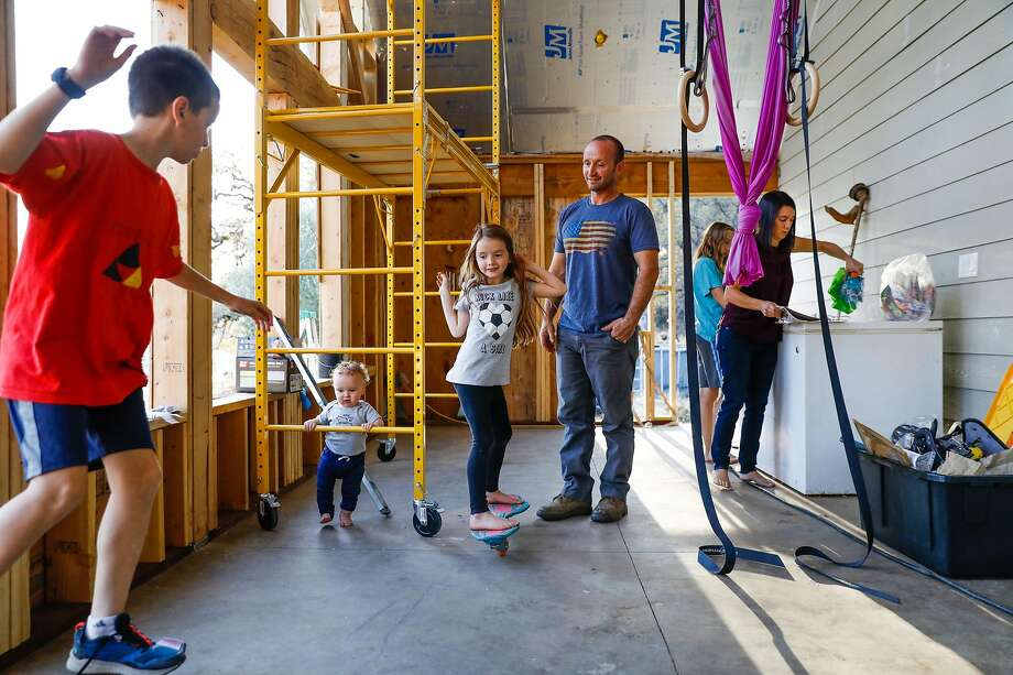 (l-r) Adrik Dyer, 11, Lochlan Dyer, 11-months, Emery Dyer, 8, Jason Dyer, Branson Dyer, 14,and Mikalia Dyer hang out outside on the unfinished addition to their house in Paradise, California, on Tuesday, Nov. 12, 2019. Jason, a firefighter, was trapped on a small road during the Kincade fire last month and was forced to deploy his fire shelter to help save himself and two other civilians in Geyserville. Photo: Photos By Gabrielle Lurie / The Chronicle