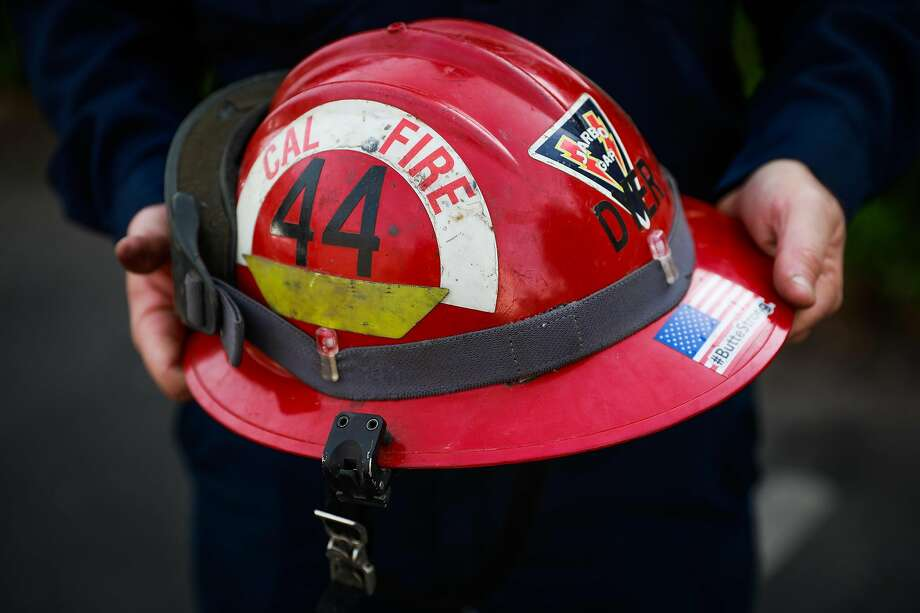 Dyer shows off the helmet he was wearing during a near-death experience fighting the Kincade Fire. Photo: Gabrielle Lurie / The Chronicle
