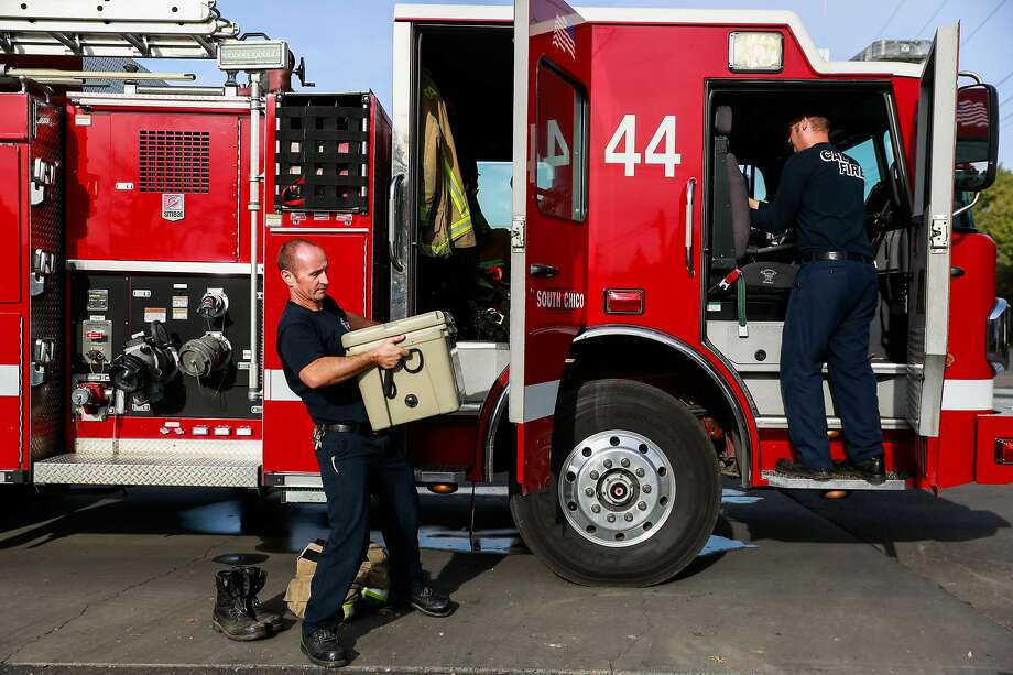 Firefigher Jason Dyer (left) and his partner firefighter Peter Sims maintain the fire engine in the morning to make sure everything is working properly at his fire station in Chico, California, on Wednesday, Nov. 13, 2019. Jason was trapped on a small road during the Kincade fire last month and was forced to deploy his fire shelter to help save himself and two other civilians in Geyserville. Photo: Gabrielle Lurie / The Chronicle