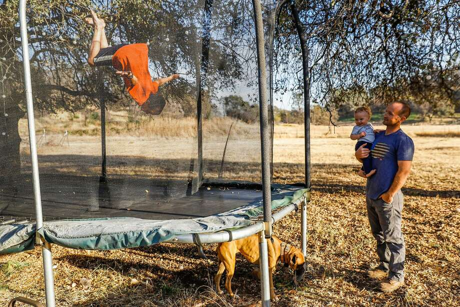 (l-r) Adrik Dyer, 11, does flips on the trampoline as his father Jason Dyer, holds his neborn son Lochlan, 11-months, outside their house in Paradise, California, on Tuesday, Nov. 12, 2019. Jason, a firefighter, was trapped on a small road during the Kincade fire last month and was forced to deploy his fire shelter to help save himself and two other civilians in Geyserville. Photo: Gabrielle Lurie / The Chronicle