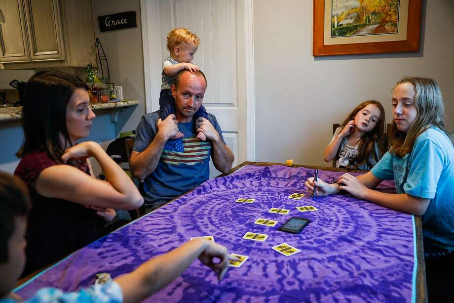 (l-r) Mikalia Dyer, Jason Dyer and their children Lochlan, 11-months, Emery, 8, Branson, 14, and Keegan, 12 (far left) play One Night Ultimate Werewolf at their home in Paradise, California, on Tuesday, Nov. 12, 2019. Jason, a firefighter, was trapped on a small road during the Kincade fire last month and was forced to deploy his fire shelter to help save himself and two other civilians in Geyserville. Photo: Gabrielle Lurie / The Chronicle