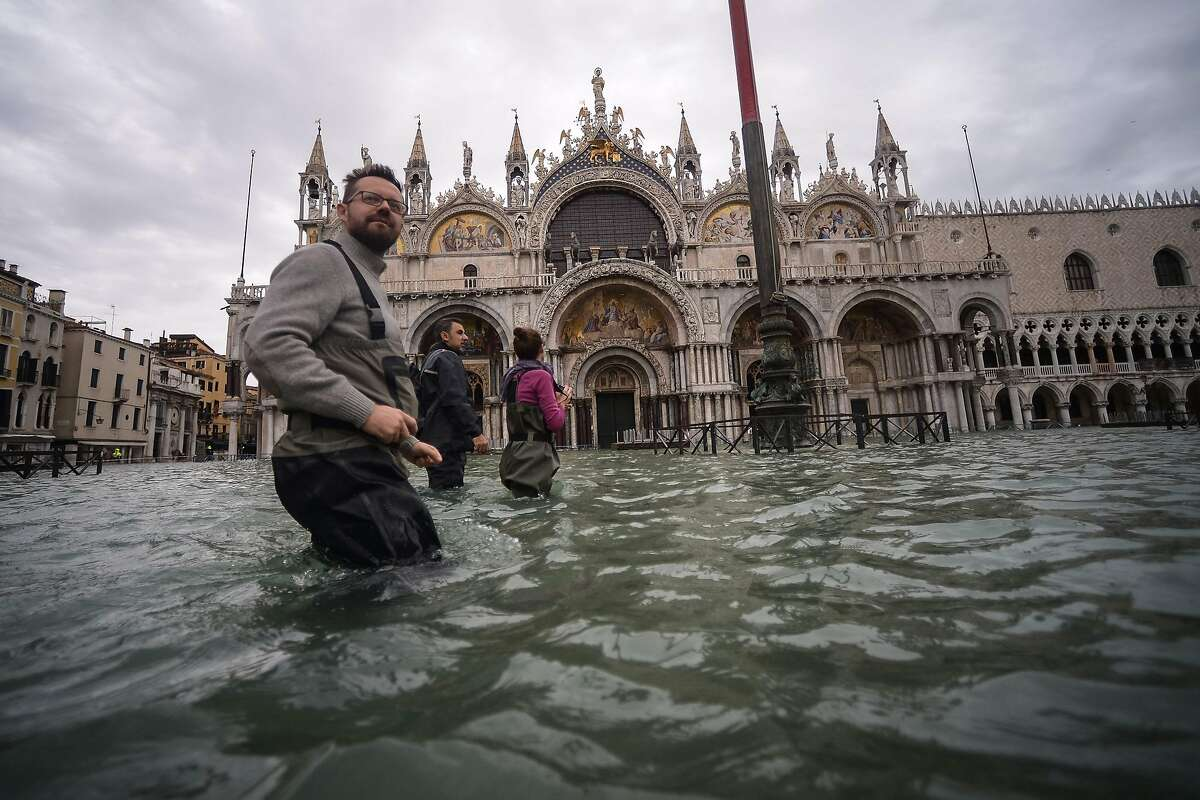 A general view shows people walking across the flooded St. Mark's Square, by St. Mark's Basilica on November 15, 2019 in Venice, two days after the city suffered its highest tide in 50 years. - Flood-hit Venice was bracing for another exceptional high tide on November 15, as Italy declared a state of emergency for the UNESCO city where perilous deluges have caused millions of euros worth of damage.