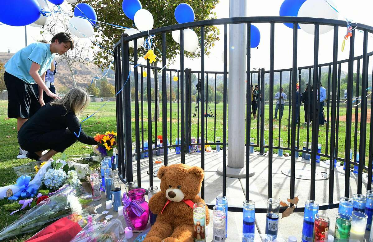 Flowers are dropped off at a makeshift memorial in Central Park, not far from Saugus High School on November 15, 2019 in Santa Clarita, California - A teenage boy gunned down fellow students at a California high school on his 16th birthday on November 14, 2019, killing two and wounding another three before turning the pistol on himself. The gunman was taken into custody in