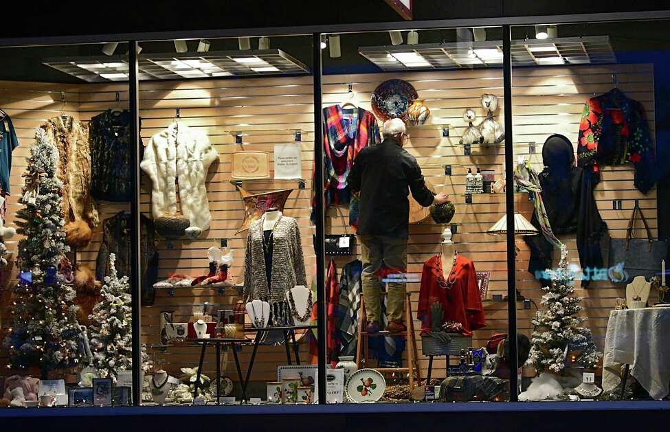 A man is seen decorating Pearl Grant Richmans store front window for the holidays in Stuyvesant Plaza on Thursday, Nov. 12, 2019 in Albany, N.Y. (Lori Van Buren/Times Union)