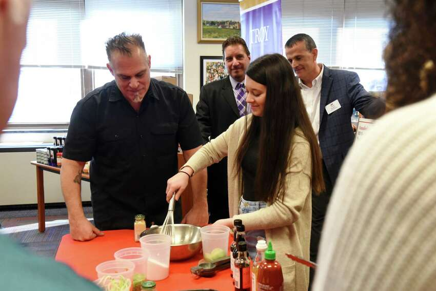 Troy High School senior Brianna Nagengast-McHale, right, makes a meal under the guidance of Chef Ric Orlando, left, during an announcement that Hannaford donated nearly $300,000 to establish food pantries in dozens of schools in New York on Friday, Nov. 15, 2019, at Troy High School in Troy N.Y. (Will Waldron/Times Union)