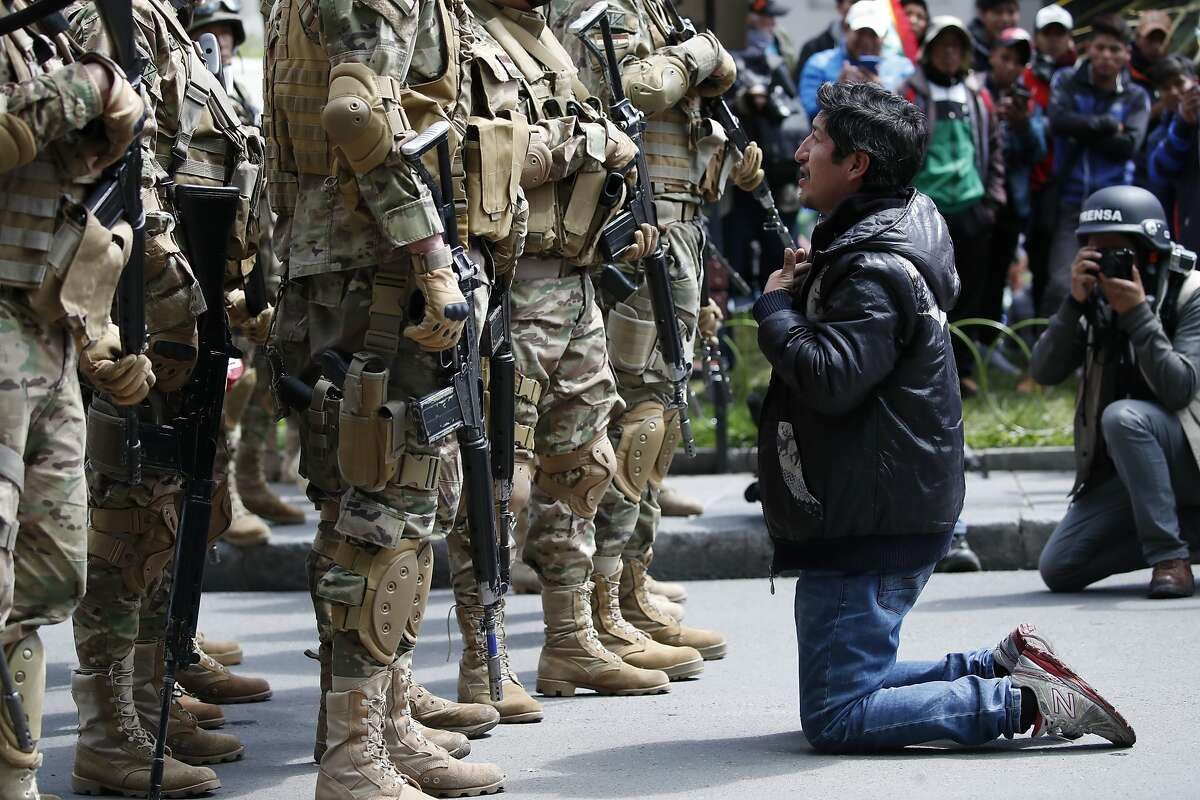 A backer of former President Evo Morales kneels in front of soldiers guarding a street in downtown La Paz, Bolivia, Friday, Nov. 15, 2019. Morales resigned on Nov. 10 at military prompting following massive nationwide protests over suspected vote-rigging in an election in which he claimed to have won a fourth term in office. An Organization of American States audit of the vote found widespread irregularities.(AP Photo/Natacha Pisarenko)
