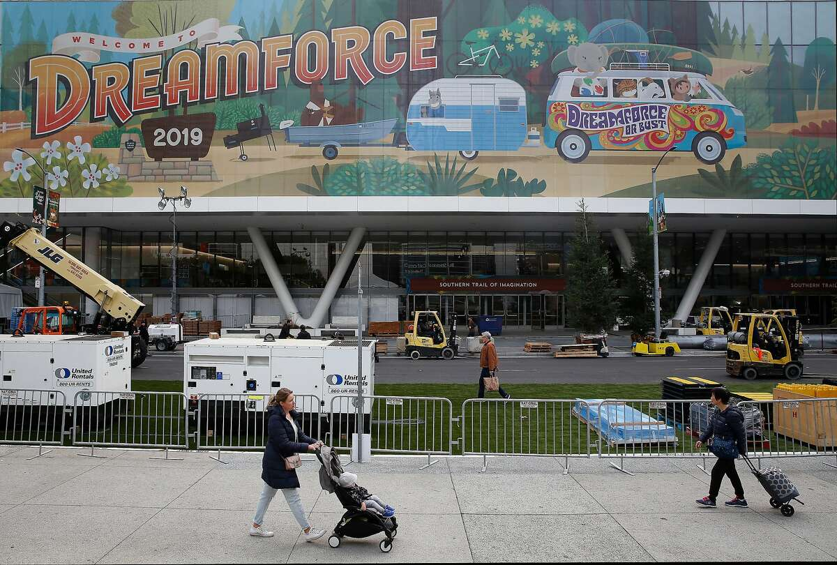 Pedestrians on Howard Street walk past signage for Dreamforce displayed on Moscone Center days before the start of Dreamforce on Friday, November 15, 2019 in San Francisco, Calif.