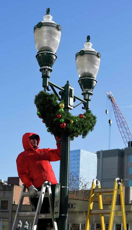 Marvin Vasquez of Christmas Lighting Company puts up Holiday Decor in Columbus Park on Nov. 13, 2019 in Stamford, Connecticut. Photo: Matthew Brown / Hearst Connecticut Media / Stamford Advocate