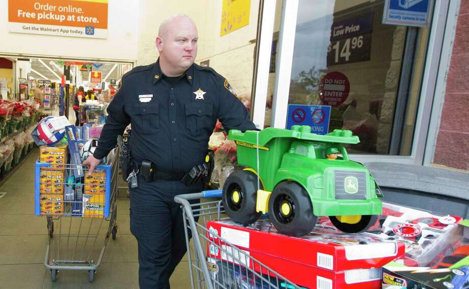 Lee Knudsen, specialist with the Montgomery County Sheriff's Office, helps wheel out toys, gifts and more than 365 bicycle as part of Operation Blue Elf, which provides toys for local children in need, at Walmart on Wednesday, Dec. 12, 2018, in Conroe. Photo: Jason Fochtman, Houston Chronicle / Staff Photographer / © 2018 Houston Chronicle