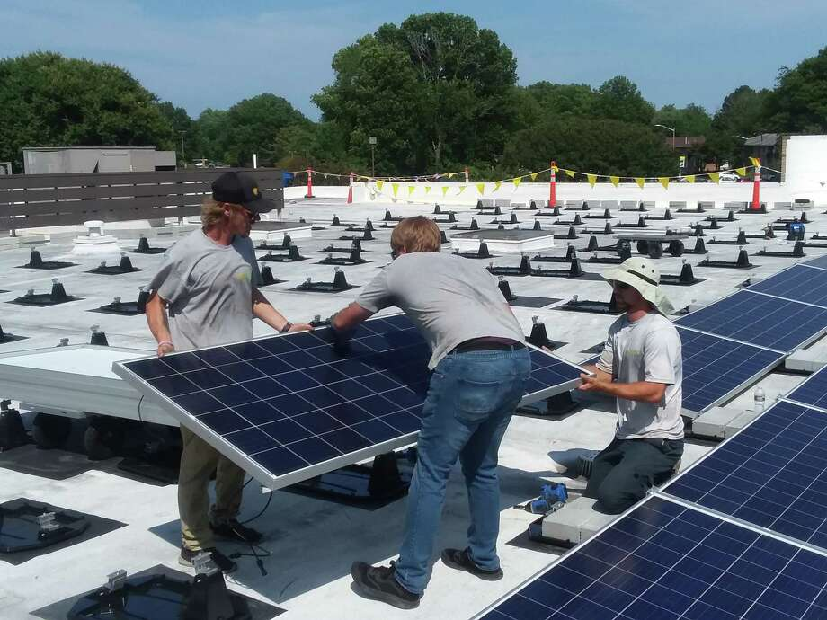 Workers install solar panels at Immaculate Conception Catholic Church in Hampton, Va. Photo: Handout Courtesy Of John Grace / Courtesy