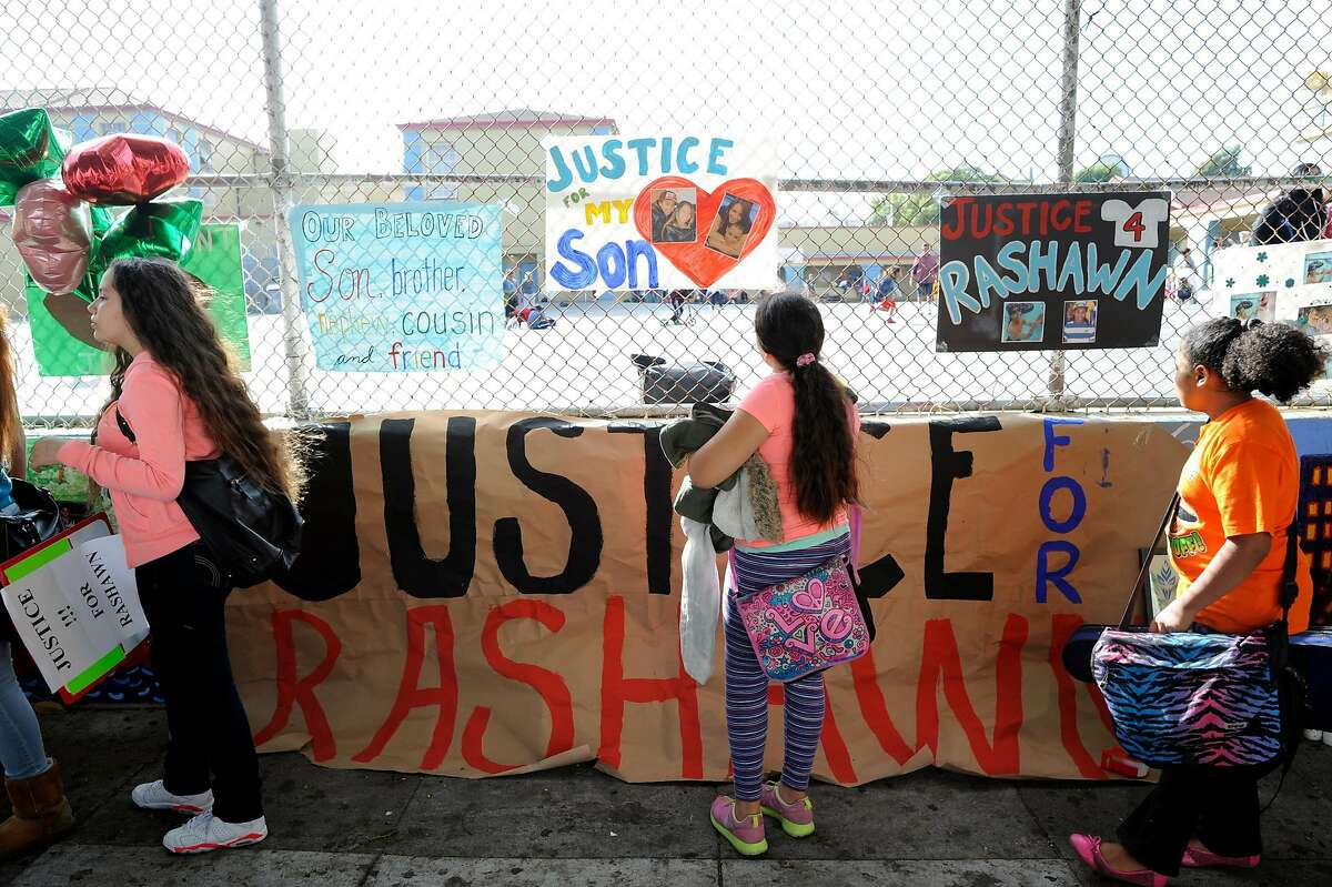 Students stop and look at the signs during a demonstration for Rashawn Williams, a 14-year-old student killed by a classmate, at Buena Vista Horace Mann School in San Francisco, CA, October 10, 2014. The family of Rashawn Williams, a 14-year-old honor roll student and football star who was killed by a classmate, is calling for the San Francisco district attorney to charge the 14-year-old boy accused of killing Rashawn as an adult.