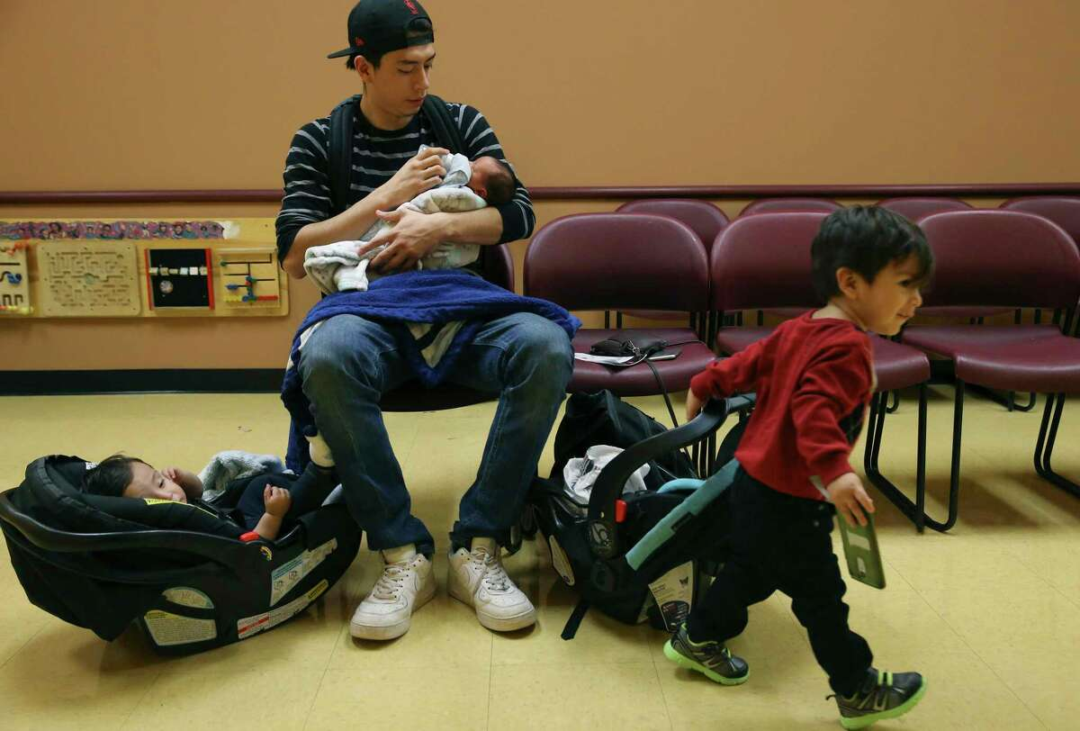 It's been estimated that 11 percent of children in Texas are uninsured. That's not OK. Here, a father sits with his children at the South Flores Women, Infant and Children Clinic.