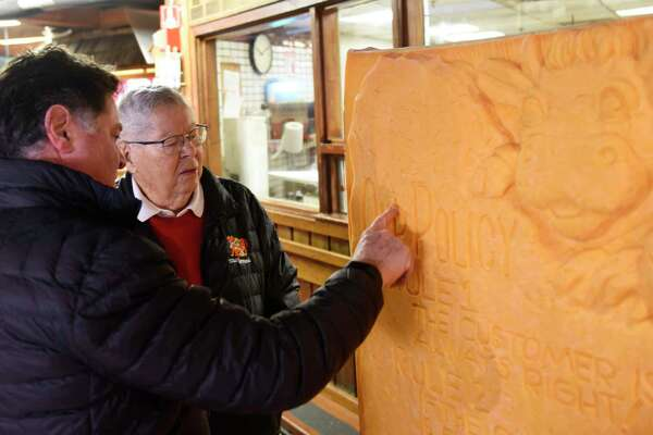 "President and CEO Stew Leonard Jr., left, and his father Founder Stew Leonard look upon a 3,462 pound carved block of cheddar cheese displayed at Stew Leonard's grocery store in Norwalk, Conn. Monday, Dec. 10, 2018. Norwalk Mayor Harry Rilling joined the Stew Leonard family to unveil the soon-to-be Guinness Book of World Records' largest cheese sculpture. The mammoth cheddar sculpture has carved into it the longtime Stew Leonard's customer service motto from its ""Customer Service Rock of Commitment."" More than 500 cows contributed milk to the record breaking cheese, which was carved in East Meadow, N.Y."